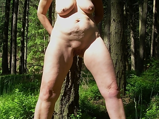 Mature redhead naked by the lake