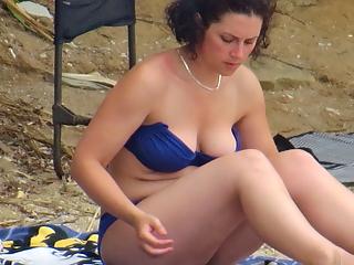 Busty milf read on the beach